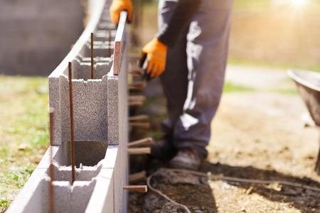 Hormigón: Albañil sofocar otra fila de ladrillos en el sitio