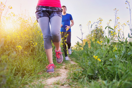 woman in field: Young couple running outside in spring canola field Stock Photo