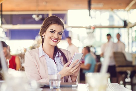 comercial: Attractive young woman with smart phone in cafe