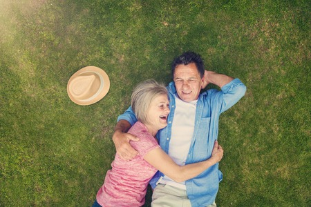 hugs: Beautiful seniors lying on a grass in a park hugging