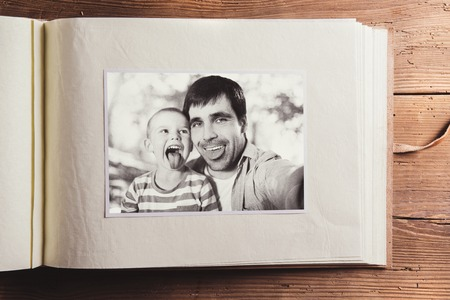family photo: Fathers day composition - photo album with a black and white photo. Studio shot on wooden background.