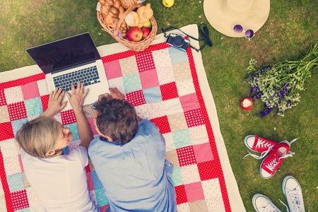 Mooie senioren met een notebook met een picknick in de natuur Stockfoto