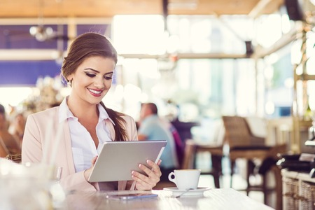 Attractive young woman with tablet in cafe photo