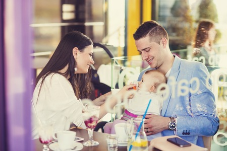 Young parents with their cute baby daughter in cafe photo