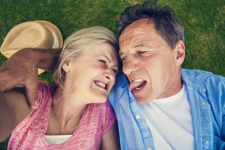 funny face: Beautiful seniors lying on a grass in a park taking selfie