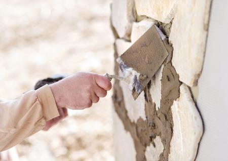 stonemason: Mason putting decorative natural stones on a wall
