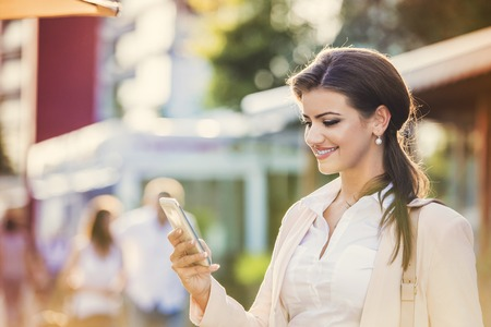 businness: Attractive young businness woman with smart phone in the city
