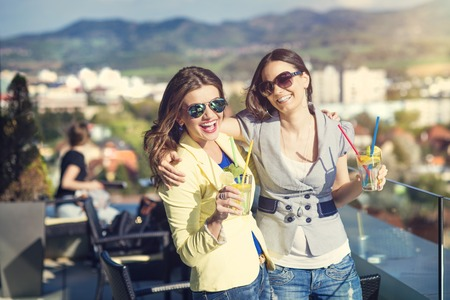 tomando alcohol: Dos mujeres hermosas que se divierten en un bar Foto de archivo