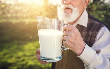 Senior farmer with milk in a glass jug outside in green nature Stock Photo