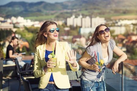 personas reunidas: Dos mujeres hermosas que se divierten en un bar Foto de archivo