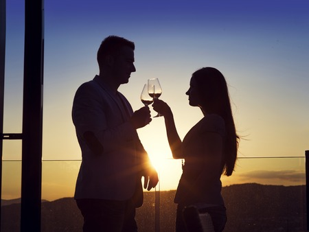 Beautiful young couple drinking wine on a terrace of a bar