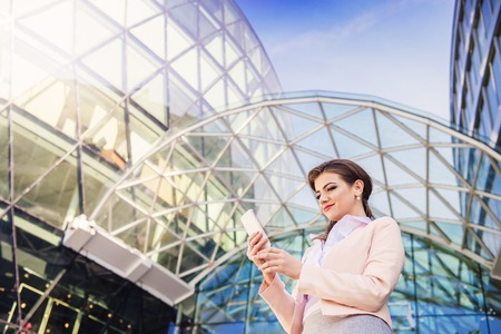 comercial: Attractive young business woman with smart phone in the city Stock Photo