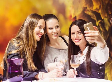 Three beautiful women having fun in a wine bar Stock Photo