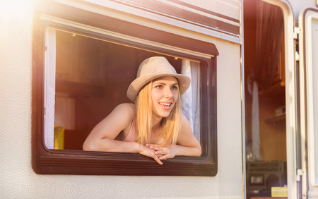 camper trailer: Beautiful young woman sitting in a camper van on a summer day