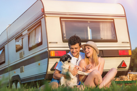 Beautiful young couple in front of a camper van on a summer day Stock Photo