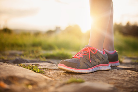 trainers: Unrecognizable runner feet with sunlight