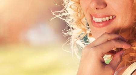 smile teeth: Unrecognizable attractive young woman outside in summer nature Stock Photo
