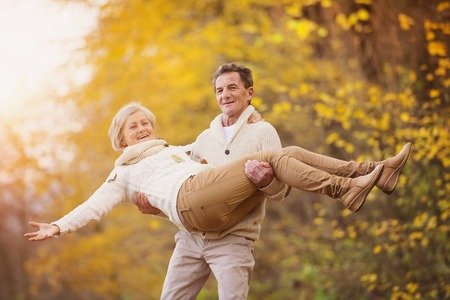 active seniors: Active seniors having fun and playing with the leaves in autumn forest Stock Photo