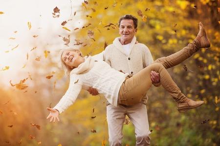 divercio n: Mayores activos divirtiéndose y jugando con las hojas en el otoño de los bosques Foto de archivo
