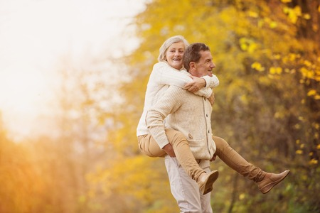 people in action: Active seniors having fun and playing with the leaves in autumn forest Stock Photo