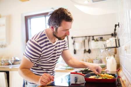 cooking healthy: Hombre en la cocina preparando langostinos