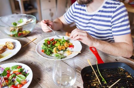 hombre comiendo: Hombre irreconocible comer gambas, ensalada y pan juntos