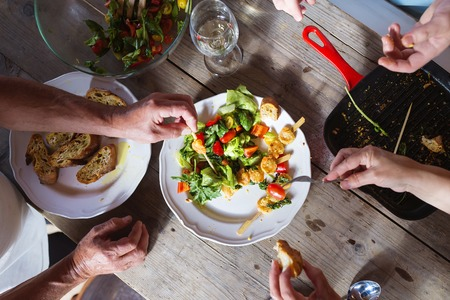 unrecognizable people: Unrecognizable people eating prawns, salad and bread together Stock Photo