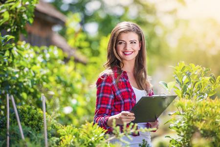 portapapeles: Mujer joven oustide en la naturaleza jardinería verde Foto de archivo