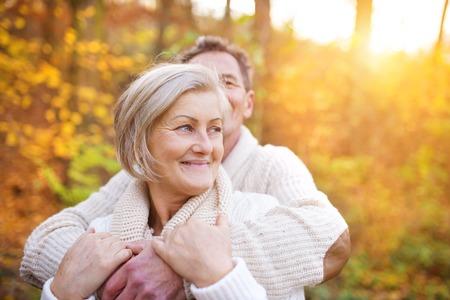 pareja abrazada: Mayores activos en una caminata en el bosque de otoño