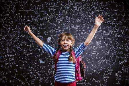 niños sonriendo: Niña linda con el bolso del scholl delante de la gran pizarra