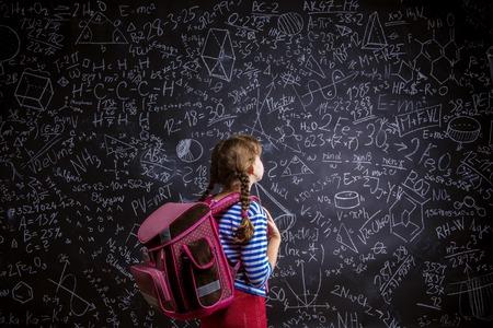mochila escolar: Niña linda con el bolso del scholl delante de la gran pizarra