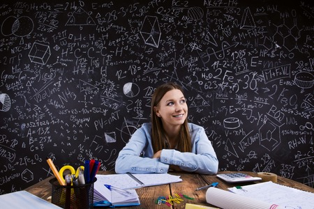 back: Beautiful student doing her homework in front of big blackboard Stock Photo