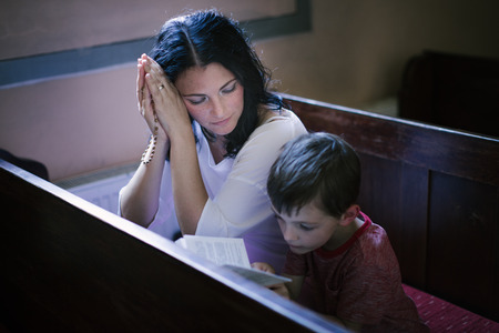 Beautiful woman with her son praying in the church Banco de Imagens