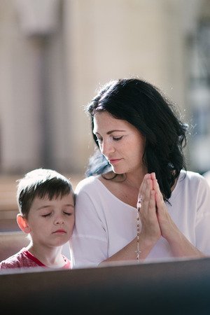 Beautiful woman with her son praying in the church Imagens