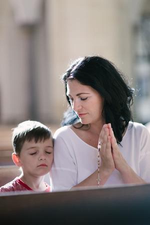mujer rodillas: Hermosa mujer con su hijo rezando en la iglesia Foto de archivo