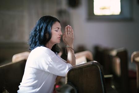 church: Hermosa mujer con un rosario rezando en la iglesia