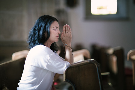 Beautiful woman with a rosary praying in the church Standard-Bild