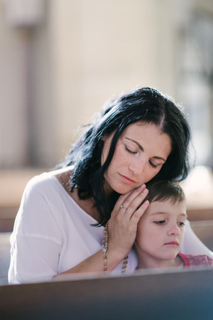 churches: Beautiful woman with her son praying in the church Stock Photo