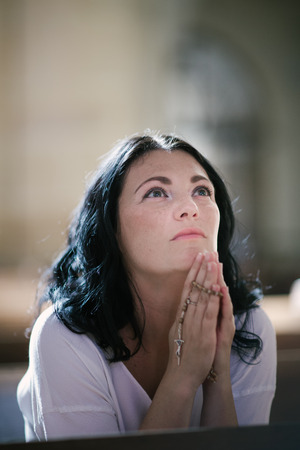 praying at church: Beautiful woman with a rosary praying in the church Stock Photo