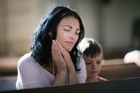 Beautiful woman with her son praying in the church 免版税图像