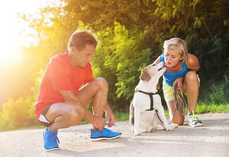 hombre viejo: Mayores activos que se preparan para una carrera con su perro al aire libre en la naturaleza verde