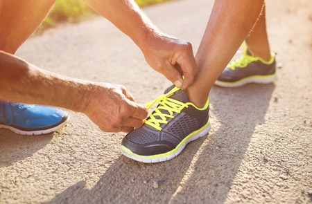 mujeres juntas: Unrecognizable seniors tying shoelaces before a run outside in green nature