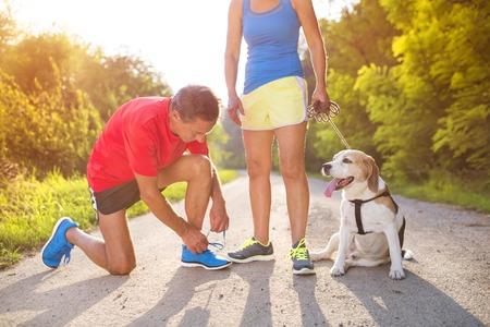 zapato: Mayores activos que se preparan para una carrera con su perro al aire libre en la naturaleza verde