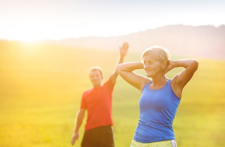sport woman: Active seniors warming up and stretching before a run outside in green nature