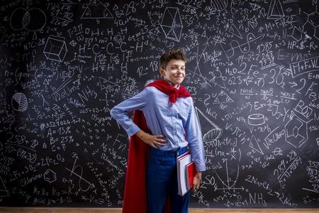 beau mec: Jeune beau garçon de l'école avec cape rouge devant grand tableau noir