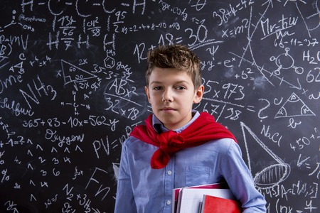 simbolos matematicos: Young handsome school boy with red cape in front of big blackboard