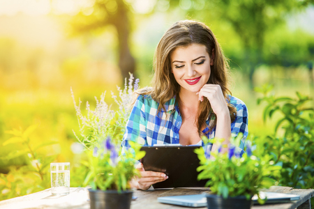 Beautiful young garden manager working outside in a garden