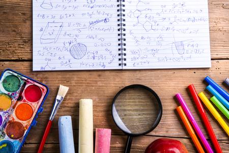 utiles escolares: Escritorio con �tiles escolares. Estudio tirado en el fondo de madera.