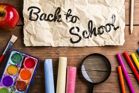 back shot: Desk with school supplies. Studio shot on wooden background. Stock Photo