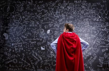 signos matematicos: Chico joven escuela guapo con capa roja delante de la gran pizarra